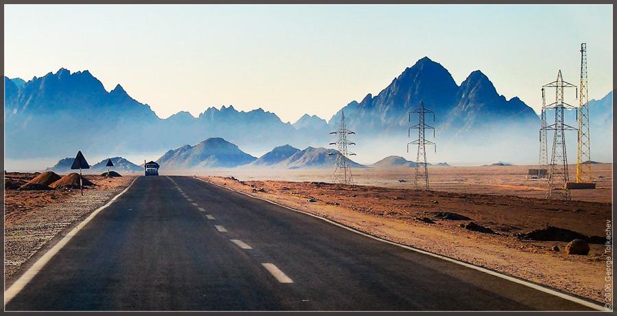 creeps out of fog...   desert, mountains, car, morning, road