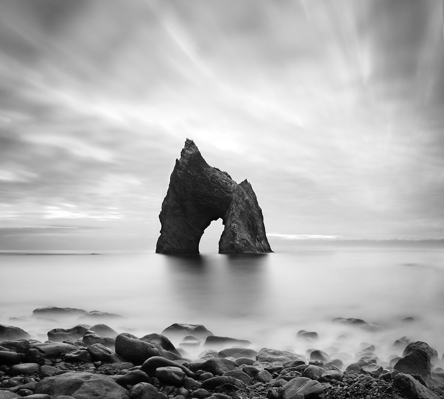 Archlike cliff | black and white, dull sky, shore, stones